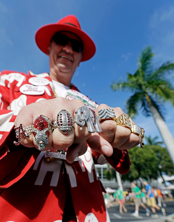 . Robin Albano of Decatur, Ala., shows off his rings outside Sun Life Stadium before the BCS National Championship college football game between the Alabama and the Notre Dame Monday, Jan. 7, 2013, in Miami. (AP Photo/Chris O\'Meara)