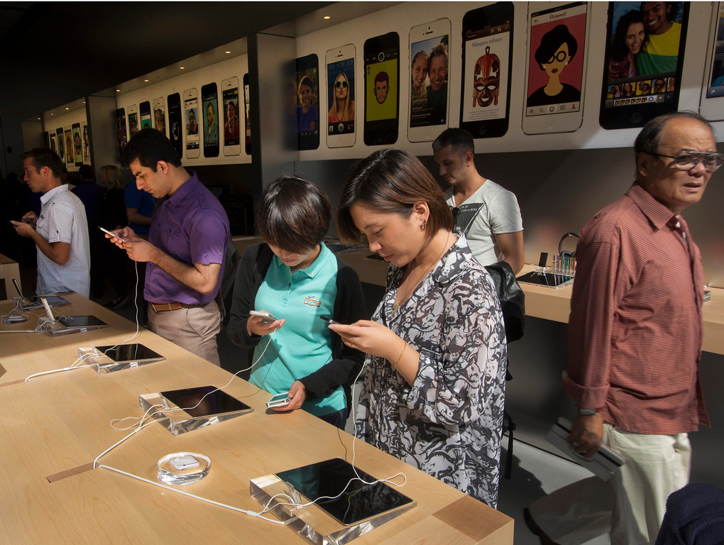 . Customers check out the latest versions of the iPhone that went on sale Friday, Sept.  20, 2013 in Montreal. Friday is the first time Apple is releasing two different iPhone models at once. (AP Photo/The Canadian Press, Ryan Remiorz)