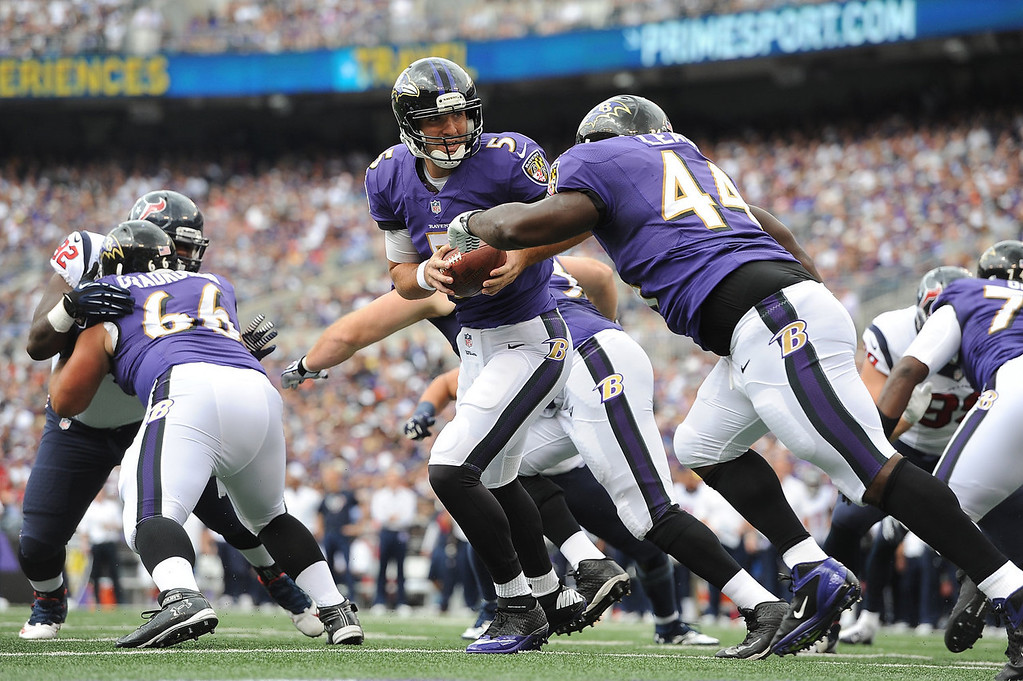 . Quarterback Joe Flacco #5 of the Baltimore Ravens hands off to Vonta Leach #44 against the Houston Texans at M&T Bank Stadium on September 22, 2013 in Baltimore, Maryland.  (Photo by Larry French/Getty Images)