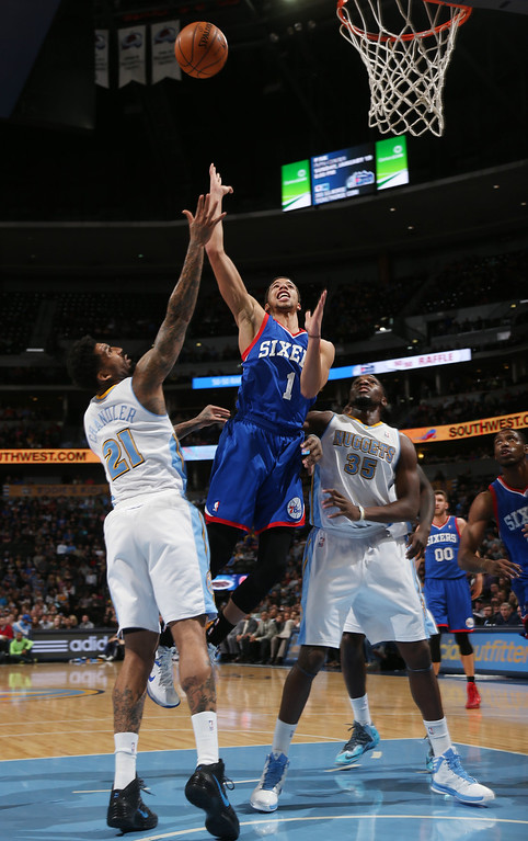 . Philadelphia 76ers guard Michael Carter-Williams, center, drives the lane for a shot between Denver Nuggets forwards Wilson Chandler, left, and Kenneth Faried during the first quarter of an NBA basketball game in Denver on Wednesday, Jan. 1, 2014. (AP Photo/David Zalubowski)