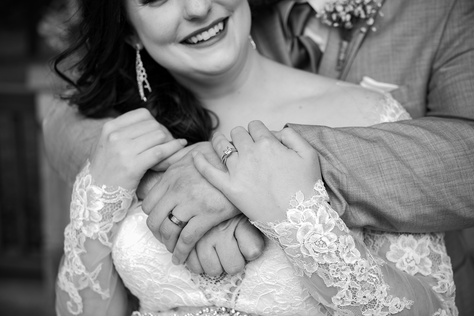 black and white photo focused on the hands and rings of a newlywed couple, the grooms arms around the bride