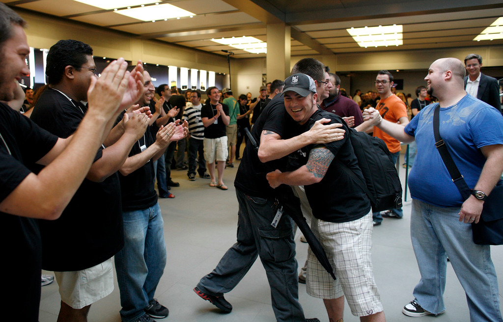 . Seth Josephson, center, of Los Angeles, Calif., gets a hug from an Apple employee as he and other customers enter the Apple Store to purchase the new Apple  iPhone Friday, June 29, 2007 in New York.  (AP Photo/Jason DeCrow)