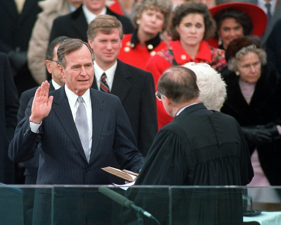 . President George Bush raises his hand Jan.20,1989 as he takes the oath of office as president of the United States outside the Capitol. Vice President  Dan Quayle watches from behind. (AP Photo/Ron Edmonds)