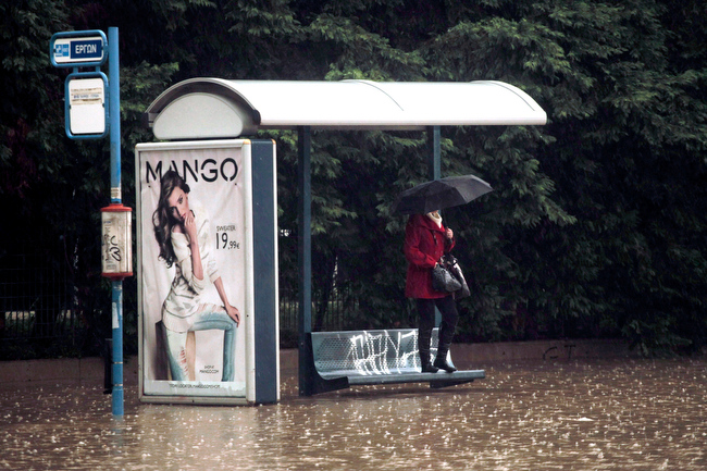 Description of . A woman shelters from the rain and the flodding at a bus stop, by standing on a bench, on a flooded highway linking Athens with its port of Piraeus, during a rainstorm on Friday, Feb. 22, 2013. Hours of heavy rainfall in Athens caused extensive flooding, inundating basements and forcing authorities to close major roads and a central subway station. The Greek fire brigade says it received more than 900 calls to pump out water in the greater Athens region Friday. (AP Photo/Petros Giannakouris)