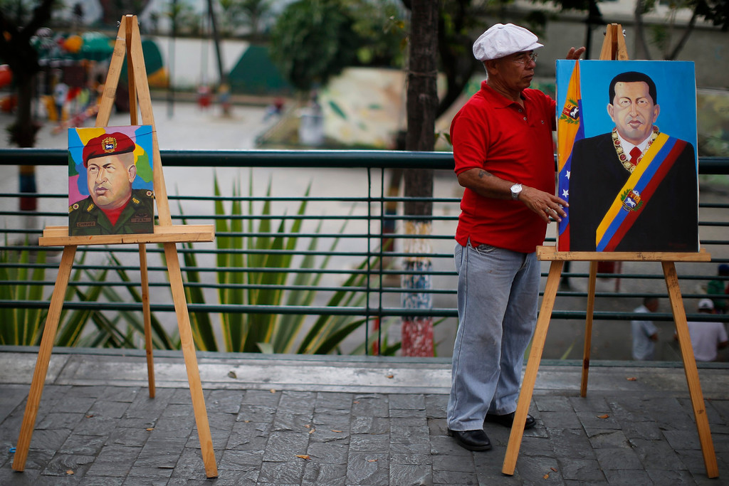 """. Painter Felix Rodriguez prepare paintings depicting Venezuelan President Hugo Chavez for sale in Caracas March 5, 2013. Chavez\'s adoring supporters prayed and wept on Tuesday over a serious setback in his battle against a cancer that threatens to end his 14-year rule of the South American OPEC member. In one of the gloomiest announcements to date on Chavez\'s health, the government said on Monday night that his breathing problems had worsened and he was suffering from a \""""severe\"""" new respiratory infection in a Caracas military hospital.   REUTERS/Jorge Silva"""