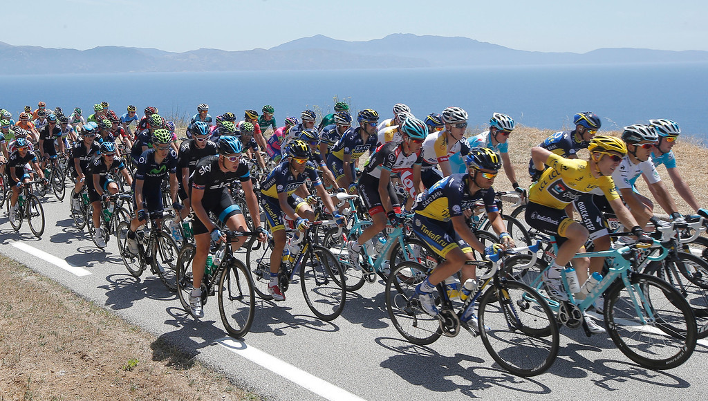 . The pack with Jan Bakelants of Belgium, wearing the overall leader\'s yellow jersey, center, rides along the Mediterranean Sea near Calcatoggio during the third stage of the Tour de France cycling race over 145.5 kilometers (91 miles) with start in Ajaccio and finish in Calvi, Corsica island, France, Monday July 1, 2013. (AP Photo/Laurent Cipriani)