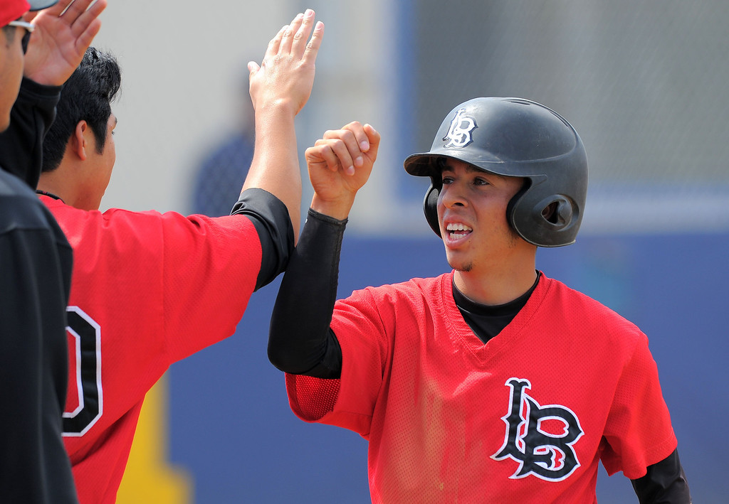 . HARBOR CITY - 04/04/2013 - (Staff Photo: Scott Varley/LANG)  Long Beach City College vs L.A. Harbor College baseball at LAHC. LBCC\'s Derrick Garcia is congratulated after scoring on a 2-run double hit by Ray Patchen.