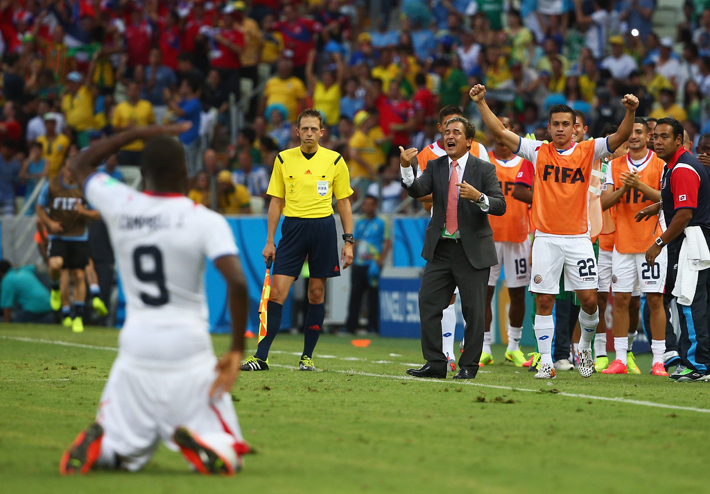 . Head coach Jorge Luis Pinto of Costa Rica and his team look on as Joel Campbell celebrates their first goal during the 2014 FIFA World Cup Brazil Group D match between Uruguay and Costa Rica at Castelao on June 14, 2014 in Fortaleza, Brazil.  (Photo by Robert Cianflone/Getty Images)