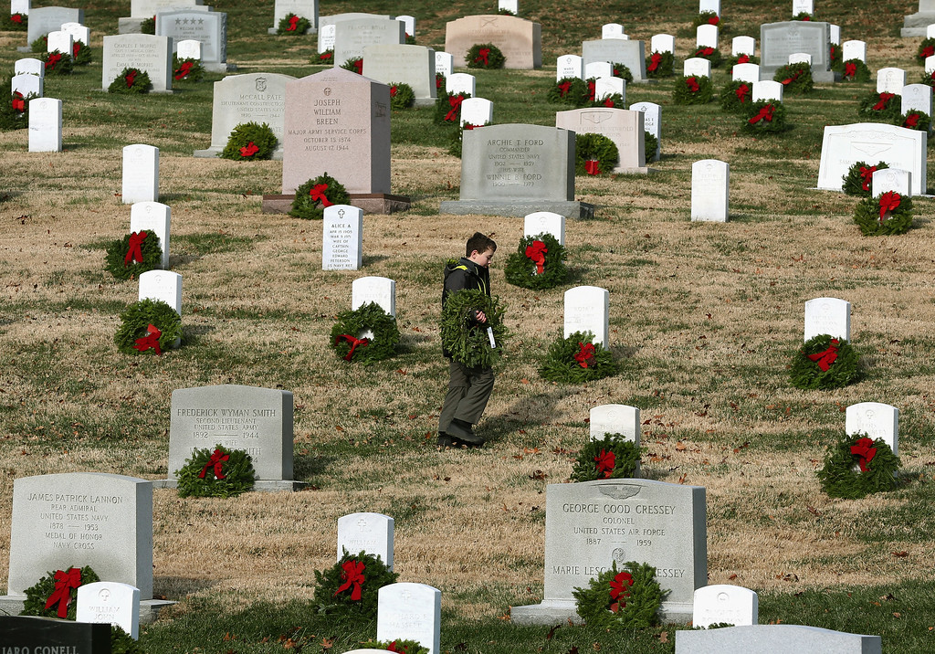 . A young boy looks for a grave to place a wreath on during the National Wreaths Across America Day at Arlington National Cemetery, December 13, 2014 in Arlington, Virginia. Volunteers placed wreaths throughout the entire cemetery in honor of Arlington\'s 150th anniversary.   (Photo by Mark Wilson/Getty Images)