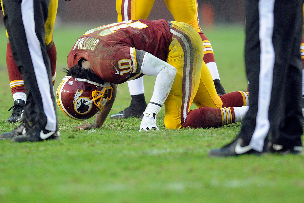 . Washington Redskins quarterback Robert Griffin III kneels on the ground after an injury during the second half of an NFL football game against the Baltimore Ravens in Landover, Md., Sunday, Dec. 9, 2012. (AP Photo/Nick Wass)