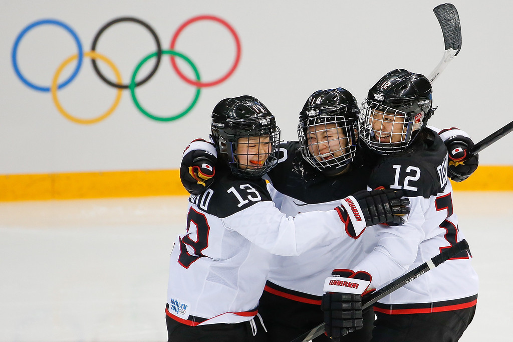 . Haruna Yoneyama of Japan, center, celebrates her goal against Germany with teammates Moeko Fujimoto, left, and Chicho Osawa, right, during the second period of the 2014 Winter Olympics women\'s ice hockey game at Shayba Arena, Tuesday, Feb. 18, 2014, in Sochi, Russia. (AP Photo/Petr David Josek)
