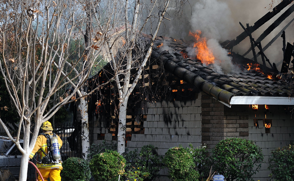 . Los Angeles County Firefighters battle a fire in the garage area that damaged a single family home. The fire started in the garage along the 1300 block of Via Verde. No injuries, but 5 cars were destroyed including two jaguars in San Dimas, Calif., on Saturday, Jan.4, 2014. 