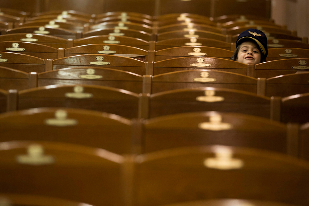 . An Ultra Orthodox Jewish boy hides from the camera during prayers for the Jewish Holiday of Purim in the Mea Shaarim neighborhood in Jerusalem, Israel, 16 March 2014. The joyful Jewish holiday of Purim celebrates the Jews\' salvation from genocide in ancient Persia, as recounted in the Scroll of Esther.  (EPA/ABIR SULTAN)
