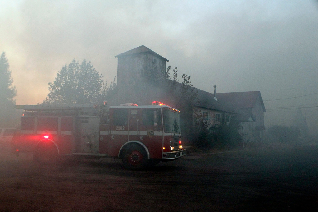 . In this Monday, Sept. 15, 2014 photo, fire crews move through a neighborhood in Weed, Calif. where a wind-driven wildfire raced through the hillside neighborhood and forced more than 1,000 people to flee the small town near the Oregon border. (AP Photo/The Record Searchlight, Greg Barnette)
