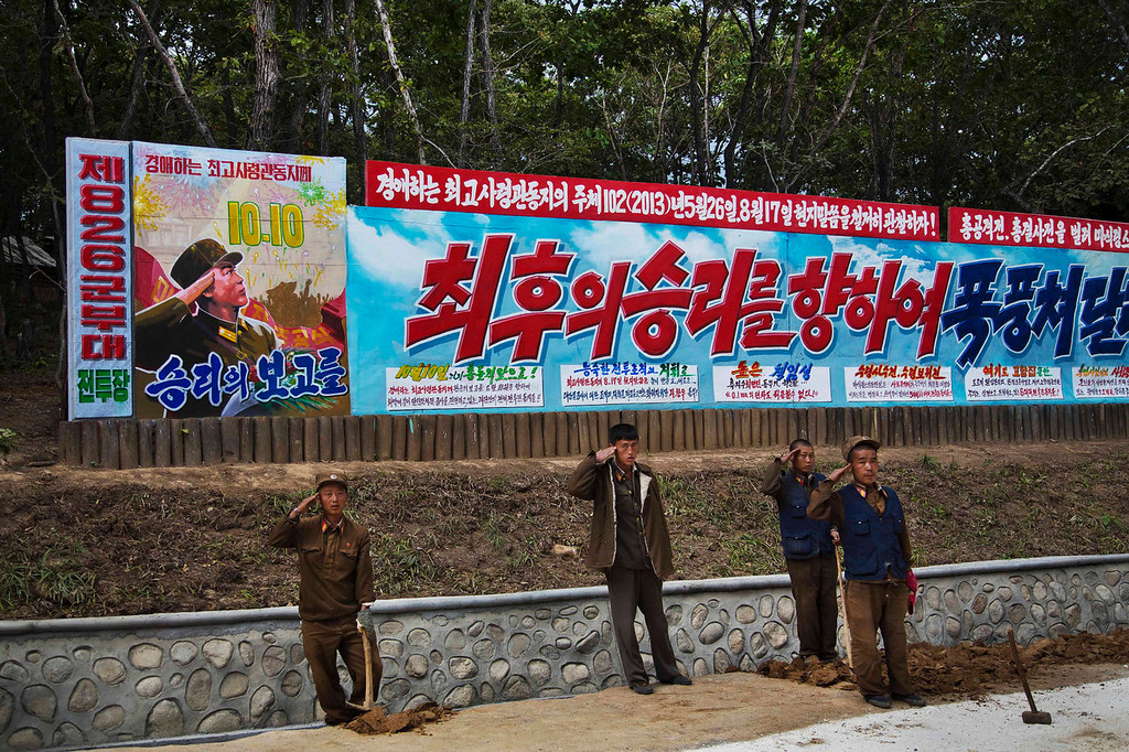 ". North Korean soldiers salute next to a propaganda billboard at a ski resort building project at North Korea\'s Masik Pass on Friday Sept. 20, 2013. The main text on the sign, in red, reads ""To The Final Victory.\"" North Korean authorities have been encouraging a broader interest in sports in the country, calling it \""the hot wind of sports blowing through Korea.\"" (AP Photo/David Guttenfelder)"