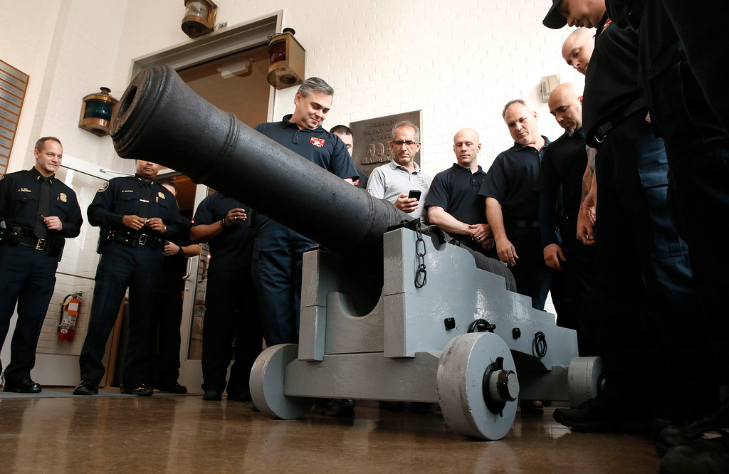 . Members of the Detroit Police Department dive team view a 18th century British cannon that was found in 2011 by Detroit police divers in the Detroit River during a training exercise in 2011. The cannon was displayed Wednesday, Dec. 10, 2014, following a three-year restoration at the Dossin Great Lakes Museum in Detroit. (AP Photo/Paul Sancya)