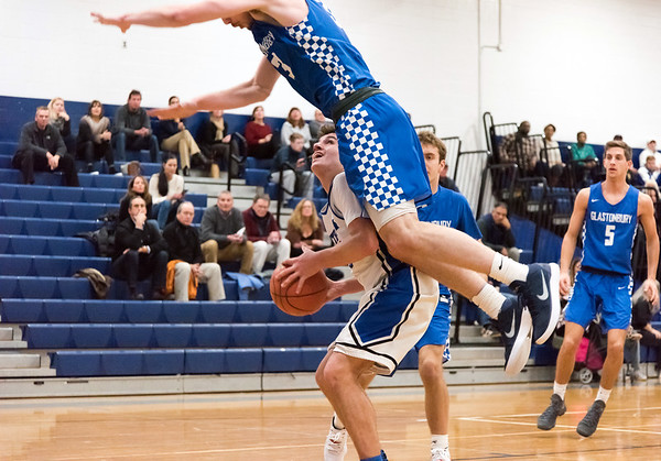 12/18/18 Wesley Bunnell | Staff Southington basketball vs Glastonbury at Southington High School on Tuesday night. Jake Napoli (20) has a defender over his back as he attempts a shot.