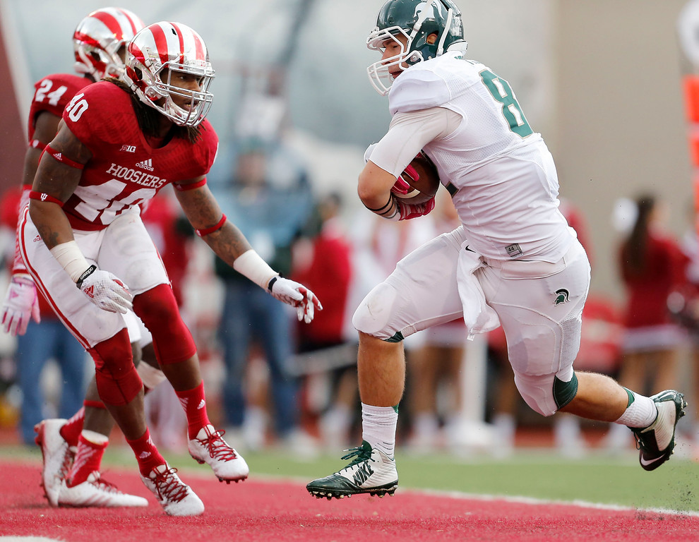 . Michigan State tight end Josiah Price (82) scores against Indiana safety Antonio Allen (40) during the first half of an NCAA college football game in Bloomington, Ind., Saturday, Oct. 18, 2014. (AP Photo/Sam Riche)
