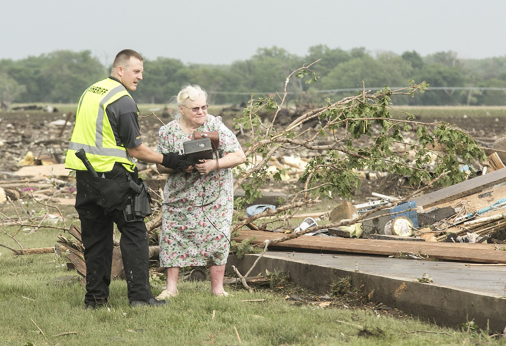 . Ruth Labenz is assisted to safety by a Stanton County Sherriff\'s officer after her home was destroyed in the town of Pilger, Neb. Monday, June 16, 2014. At least one person is dead and at least 16 more are in critical condition after two massive tornadoes swept through northeast Nebraska on Monday. (AP Photo/Mark \'Storm\' Farnik)