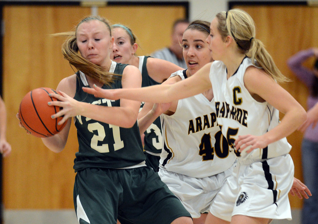. Arapahoe\'s Miaela Moore (40), center, and Carlyy Buechler (15), right, pressure Mountain Vista\'s Chelsea Pearson in the first half of the game at Arapahoe High School Gym onSaturday, Jan. 5, 2013, in Centennial, Colo. Arapahoe won 74-38. Hyoung Chang, The Denver Post