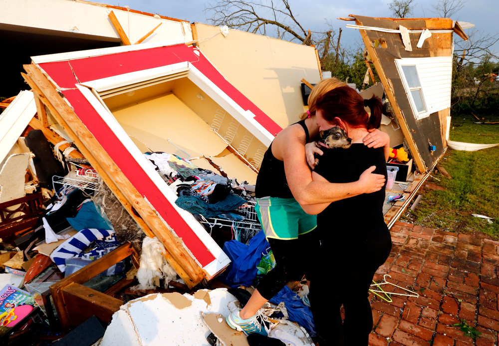 Description of . Alli Christian, left, returns Jessica Wilkinson's dog Bella to her after finding her among the wreckage of Wilkinson's home shortly after a tornado struck near 156th street and Franklin Road on Sunday, May 19, 2013  in Norman, Okla. No one was in the home when the storm struck.  (AP Photo/The Oklahoman, Steve Sisney)