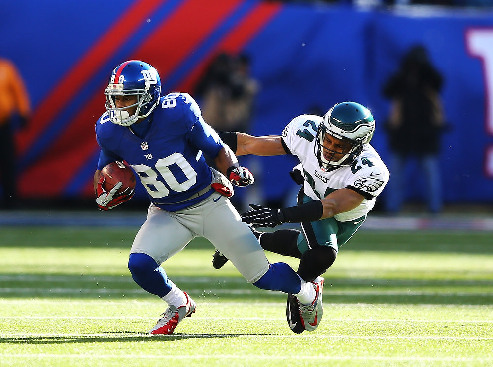 Description of . Victor Cruz #80 of the New York Giants runs with the ball after a catch against  Nnamdi Asomugha #24 of the Philadelphia Eagles  in action during their game against the at MetLife Stadium on December 30, 2012 in East Rutherford, New Jersey.  (Photo by Al Bello/Getty Images)