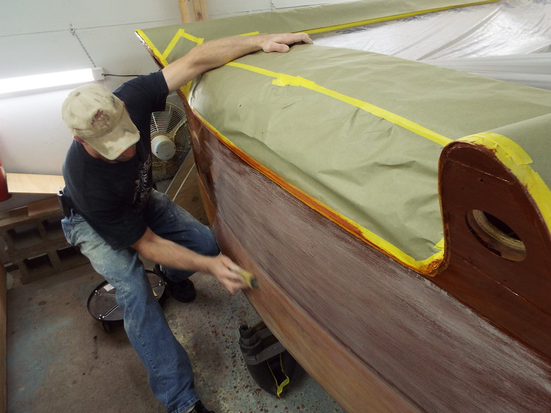 Sanding the transom after the first five coats of varnish have been applied.