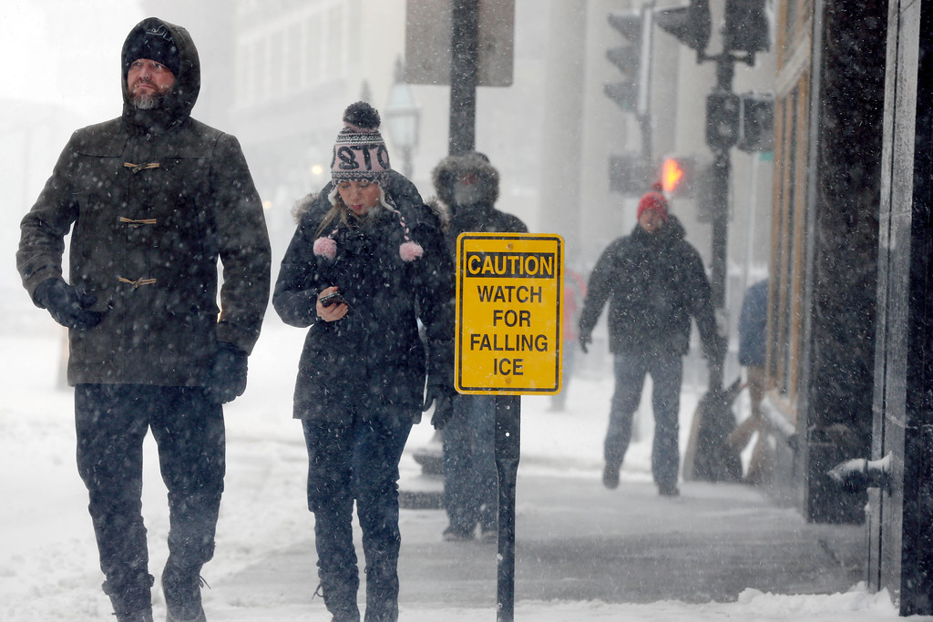. Pedestrians walk during a snowstorm, Tuesday, March 13, 2018, in Boston. (AP Photo/Michael Dwyer)