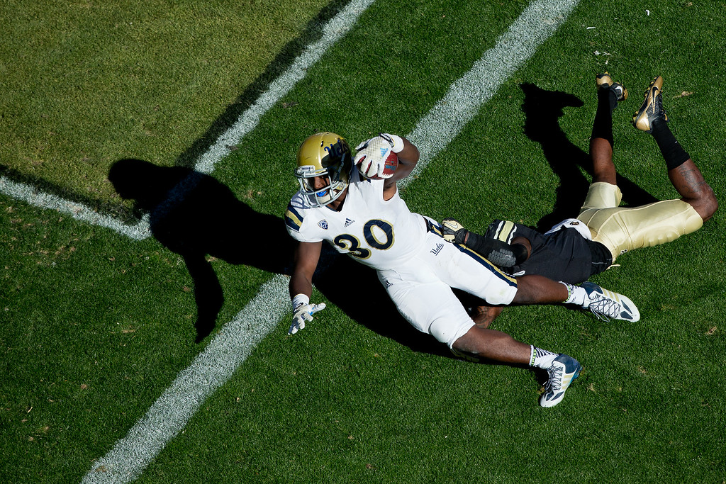 . BOULDER, CO - OCTOBER 25:  Running back Myles Jack #30 of the UCLA Bruins reaches the football over the goal line for a touchdown as cornerback Kenneth Crawley #2 of the Colorado Buffaloes during the third quarter at Folsom Field on October 25, 2014 in Boulder, Colorado. The Bruins defeated the Buffaloes 40-37 in double overtime. (Photo by Justin Edmonds/Getty Images)