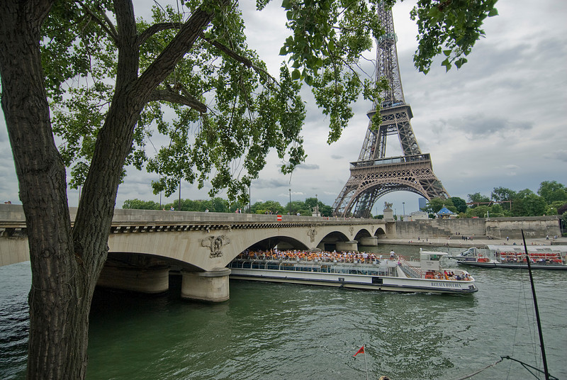 Tourist boat cruising below Eiffel Tower Bridge - Paris, France