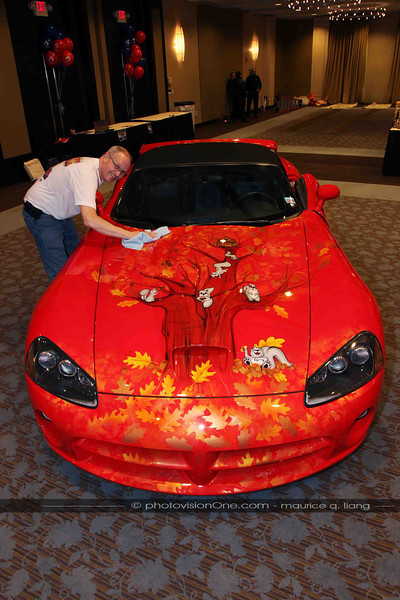 Painter Scott Miller polishes the Squirrelly car.