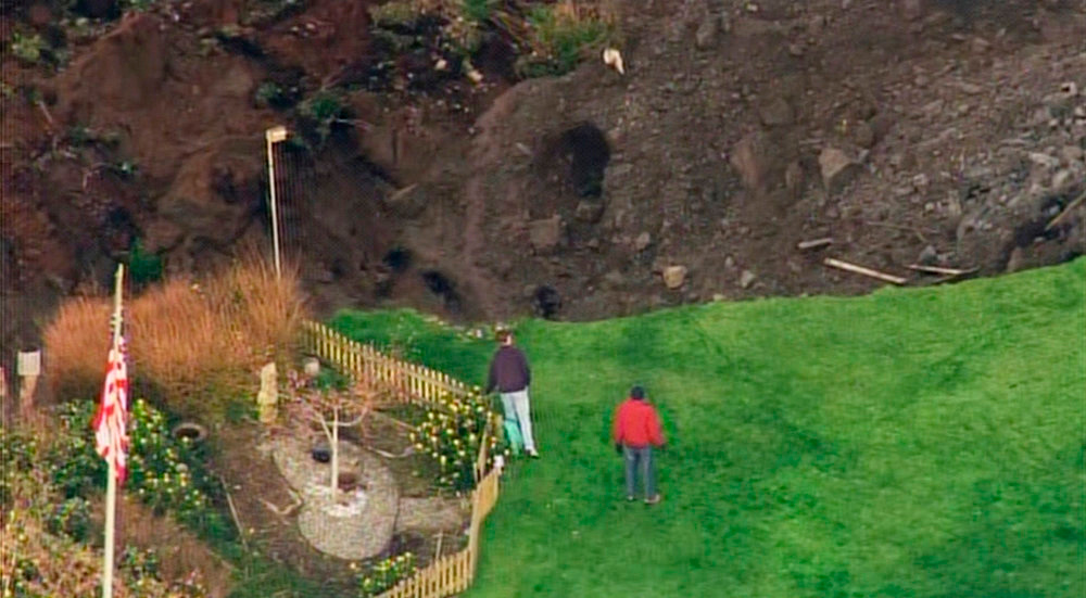 . People look over a cliff caused by a landslide on Whidbey Island, Washington, in this frame grab taken from video courtesy of KING 5 News, March 27, 2013. The landslide, which occurred early morning March 27, heavily damaged one home and is threatening over 30 others in the community of Ledgewood. REUTERS/KING 5 News/Handout