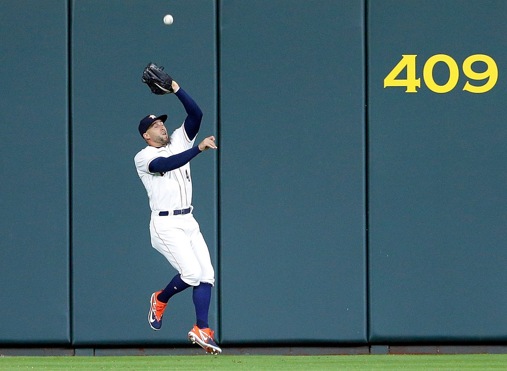 . Houston Astros center fielder George Springer (4) makes the catch at the wall on the shot by Cleveland Indians Francisco Lindor during the first inning of a baseball game Sunday, May 20, 2018, in Houston. (AP Photo/Michael Wyke)