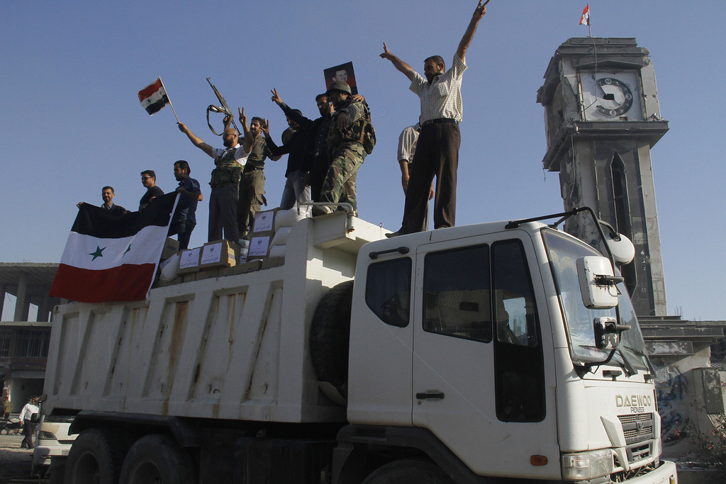 . Forces loyal to the Syrian army celebrate as they drive through the main square of Qusayr in Syria\'s central Homs province on June 5, 2013, after government forces seized total control of the former rebel-stronghold. The United States condemned the assault by Syrian troops on Qusayr, claiming the regime had had to depend on the Lebanese militant group Hezbollah to win the battle, causing tremendous suffering during a blistering 17-day assault which ended in a major battlefield success for regime forces in a war that has killed at least 94,000 people.   AFP PHOTO / STR-/AFP/Getty Images