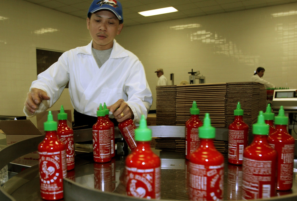 . Hang Sy collects bottles of \'Sriracha\' hot sauce during the packing phase of production Friday January 28th 2005 at Huy Fong Foods Inc. in Rosemead. (BUSINESS/staff photo by Greg Andersen)