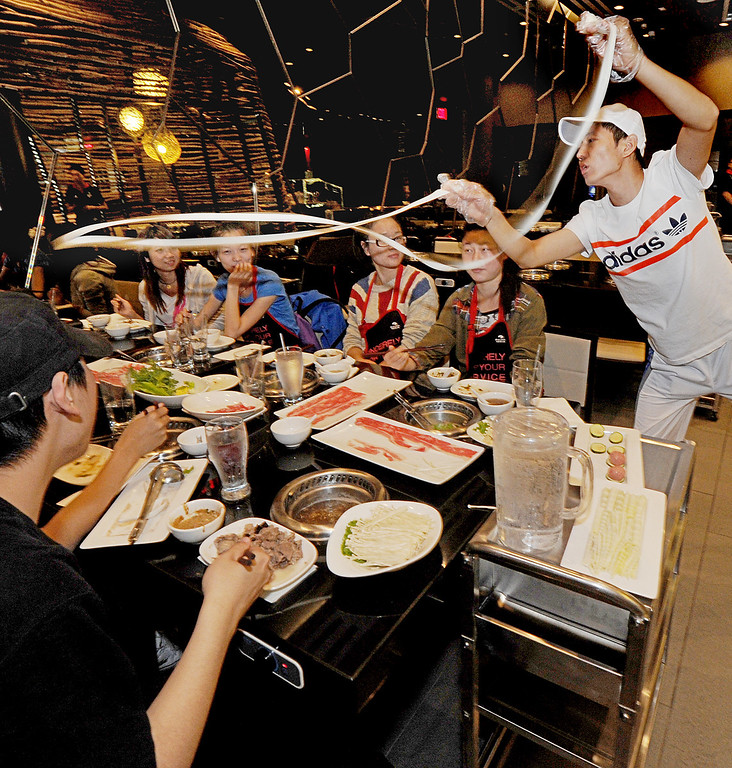 ". Hai Feng-Wong, master at ""Dancing Noodles\"", prepares noodles for table and entertains customers with his skill at Hai Di Lao Hot Pot restaurant located at Westfield Santa Anita Mall in Arcadia, Tuesday, October 8, 2013. Hai Dai Lao Hot Pot first restaurant opening in the U.S. even though there are 95 Hai Di Lao Hot Pot restaurants in China.(Walt Mancini/Pasadena Star-News)"