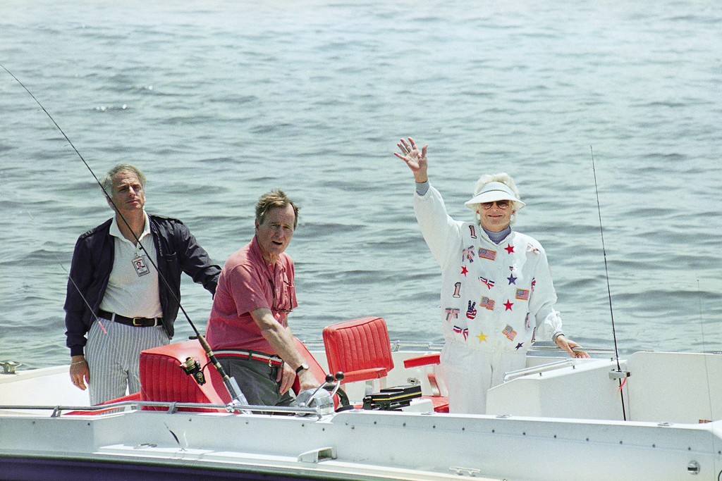 . Pres. George H. W. Bush, center, and First Lady Barbara Bush, right, wave from their boat Fidelity as stopped at a local eatery, Sunday, July 2, 1989, Cape Porpoise, Maine. The Bushes are vacationing at their home on the Maine coast for the holiday weekend. The man on the left is unidentified. (AP Photo/Herb Swanson)