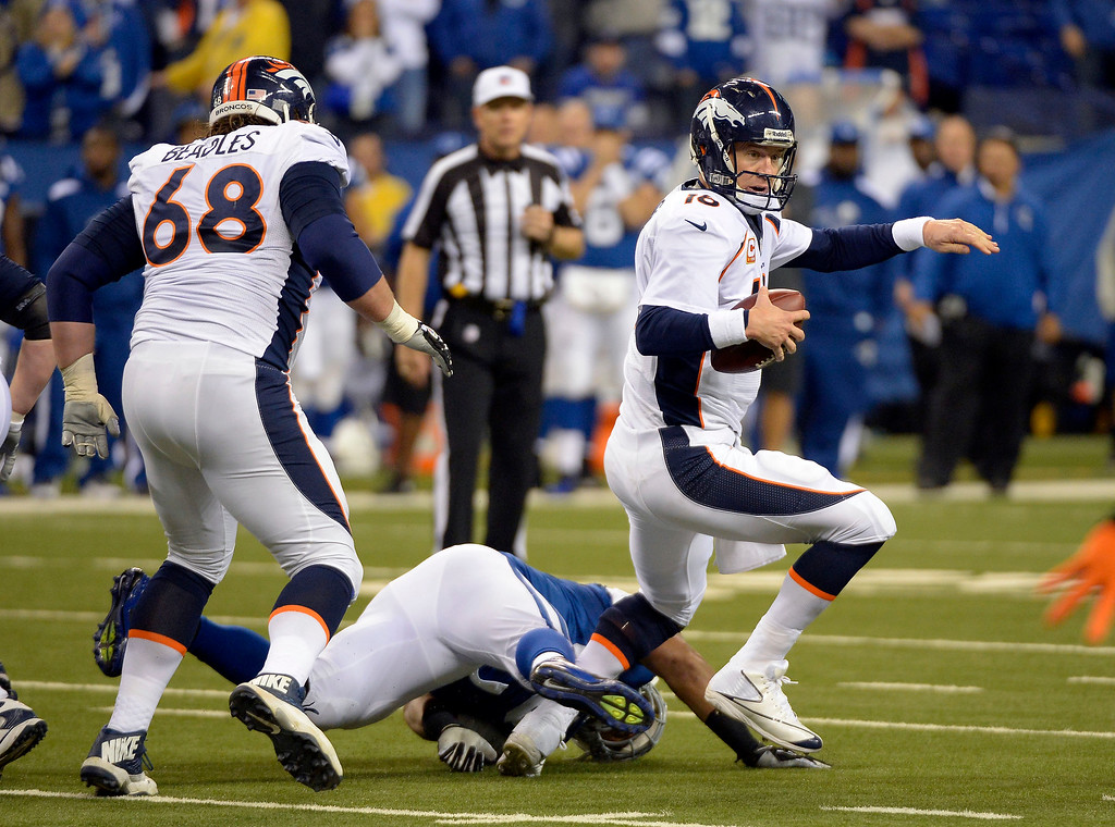 . Denver Broncos quarterback Peyton Manning (18) escapes a tackle by Indianapolis Colts defensive end Fili Moala (95) during the fourth quarter October 20, 2013 at Lucas Oil Field. (Photo by John Leyba/The Denver Post)