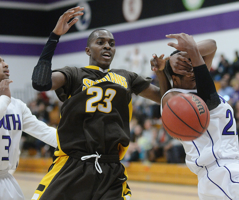 . Spartans\' junior Josh McNair (23) had the ball stripped from his hands by Rebels\' guard Keeshawn Gleason (21) in the third quarter.  Photo By Karl Gehring/The Denver Post