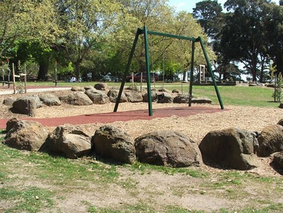 green metal swing on soft fall rubber and mulch and boulder edging