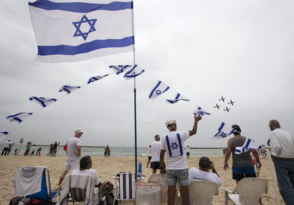 . Israelis gather to watch an air show performed by the air force, over the beach in the Mediterranean coastal city of Tel Aviv, on May 6, 2014 as Israel marks Independence Day, 66 years after the modern Jewish state was established. Israel\'s first Prime Minister David Ben-Gurion declared the existence of the State of Israel in Tel Aviv in 1948, ending the British mandate. AFP PHOTO / JACK GUEZJ