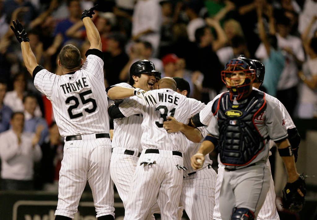 . Chicago White Soxs\' DeWayne Wise, center, celebrates with teammates Jim Thome, and Carlos Quentin after scoring on an RBI single by Orlando Cabrera as Cleveland Indians catcher Kelly Shoppach walks off the field during the tenth inning of a baseball game Tuesday, July 1, 2008, in Chicago. The White Sox defeated the Indians 3-2 in ten innings. (AP Photo/M. Spencer Green)