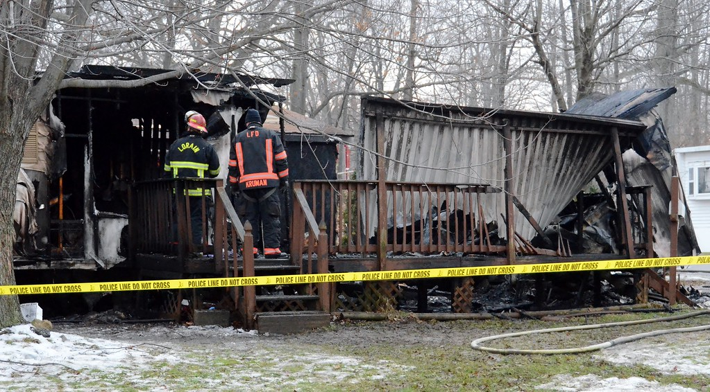 . Lorain firefighters assess the damage caused by an early morning fire Dec. 23 that claimed the life of a 9-year-old girl and injured one other person.  (Kelsey Leyva � The Morning Journal)
