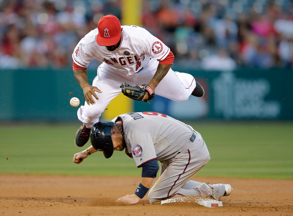. The Angels\' Howie Kendrick, top, loses the ball as he jumps over Minnesota\'s Ryan Doumit after forcing him out in the second inning. (AP Photo/Jae C. Hong)