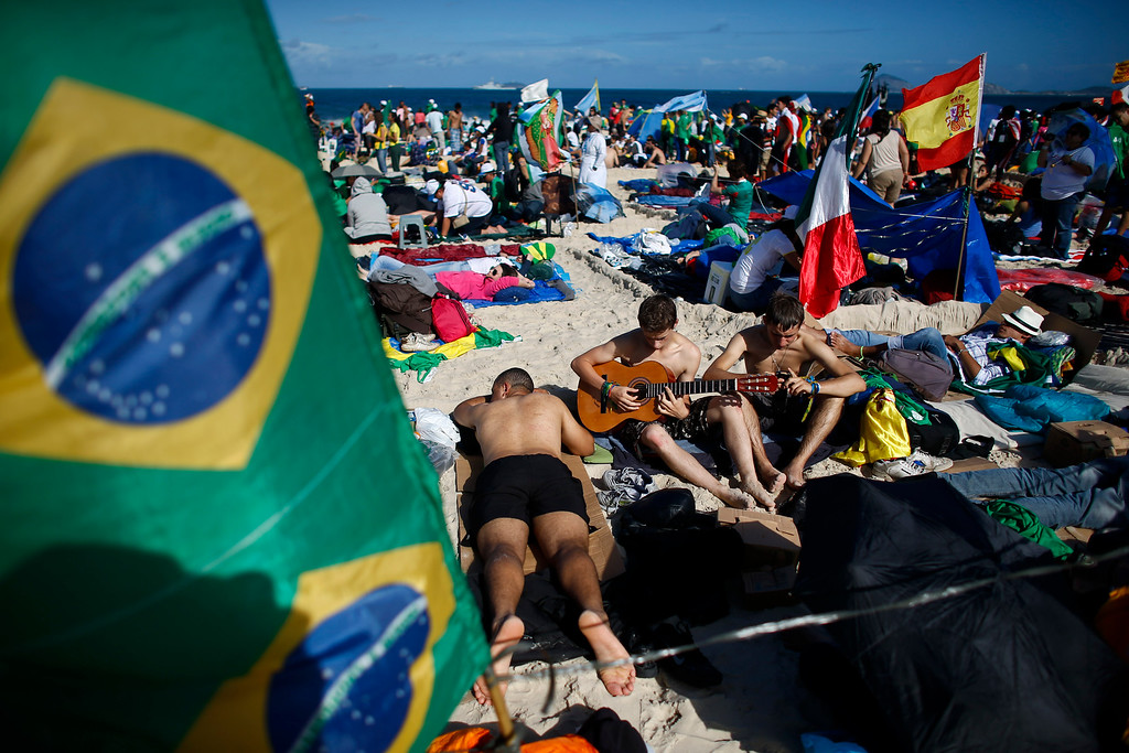 . Pilgrims play guitar and sing near a Brazilian flag, left, and a Spanish flag, right, on Copacabana beach in Rio de Janeiro, Brazil, Saturday, July 27, 2013. Pope Francis will preside over an evening vigil service on Copacabana beach that is expected to draw more than 1 million young people. (AP Photo/Victor R. Caivano)