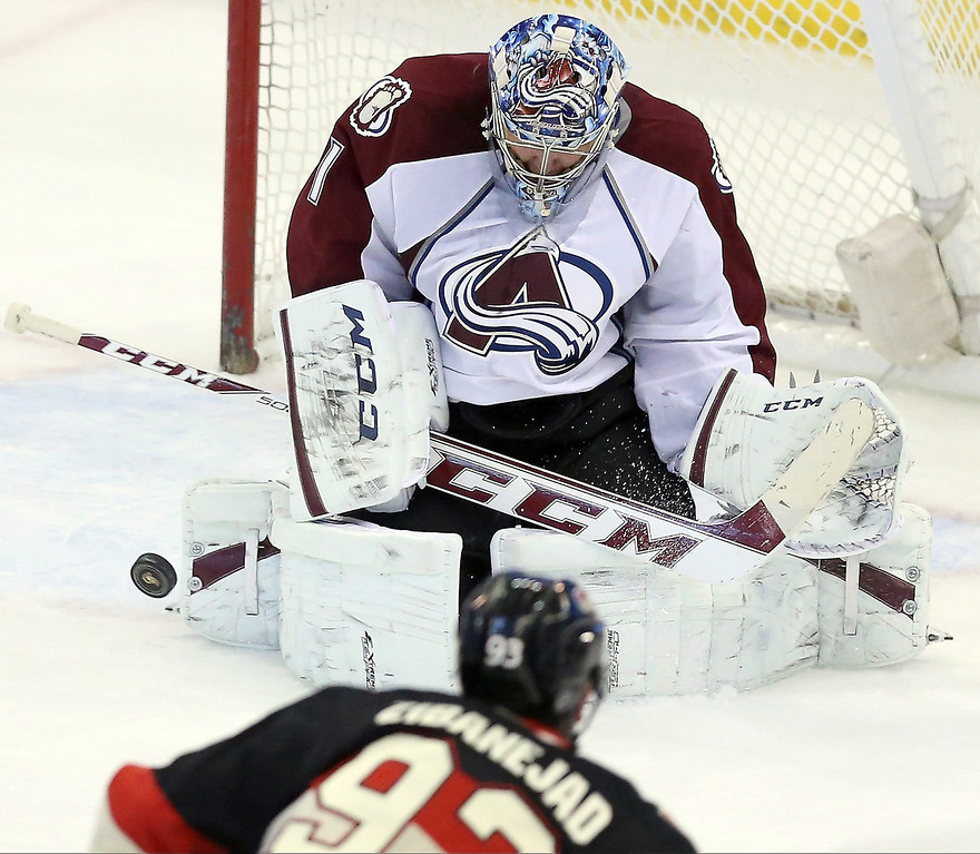 . Colorado Avalanche goaltender Semyon Varlamov, top, makes a stop against Ottawa Senators\' Mika Zibanejad during NHL hockey game action in Ottawa, Ontario, Sunday, March 16, 2014. (AP Photo/The Canadian Press, Fred Chartrand)
