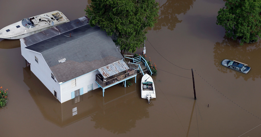 . In this aerial photo, a boat is pulled up the the front steps of a home surrounded by floodwaters near the San Jacinto River Saturday, May 30, 2015, in Channelview, Texas. The Colorado River in Wharton and the Brazos and San Jacinto rivers near Houston are the main focus of concern as floodwaters moved from North and Central Texas downstream toward the Gulf of Mexico. (AP Photo/David J. Phillip)