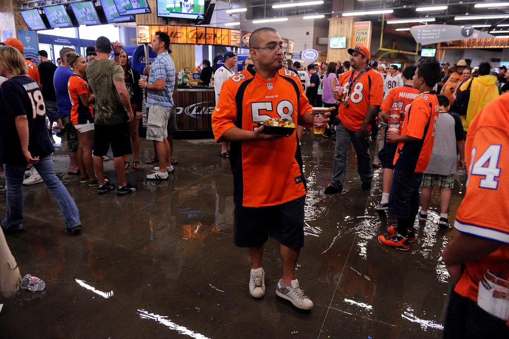 . DENVER, CO. - AUGUST 03: Fans grabbed something to eat as a thunderstorm dumped rain on the field Saturday. Denver Broncos fans waited inside Sports Authority Field Saturday night, August 3, 2013 hoping the weather would clear so that the team could practice.  Photo By Karl Gehring/The Denver Post