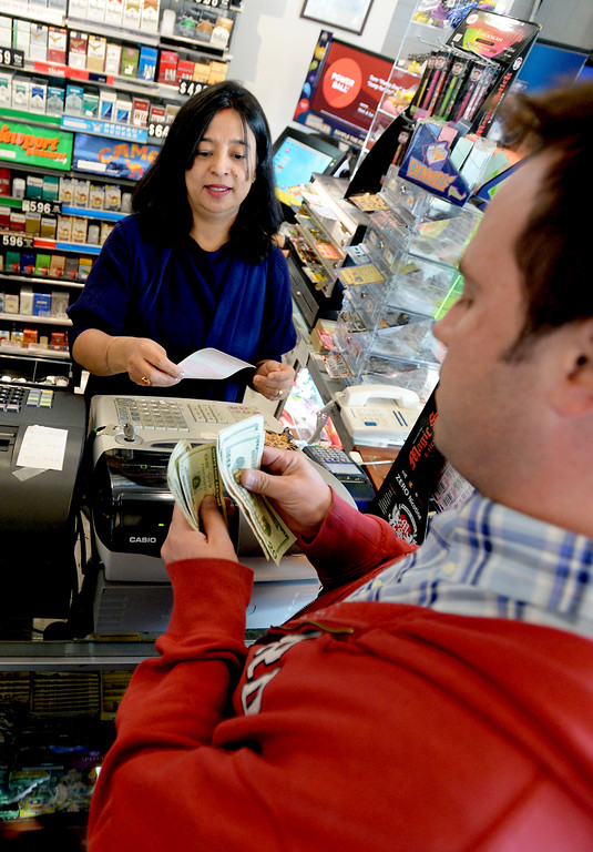 . Venus Sakha, left, owner of The General Store with her husband, sells Ryan Krug, several Powerball tickets for his coworkers on Tuesday, January 12, 2016 .  Cliff Grassmick/Boulder Daily Camera