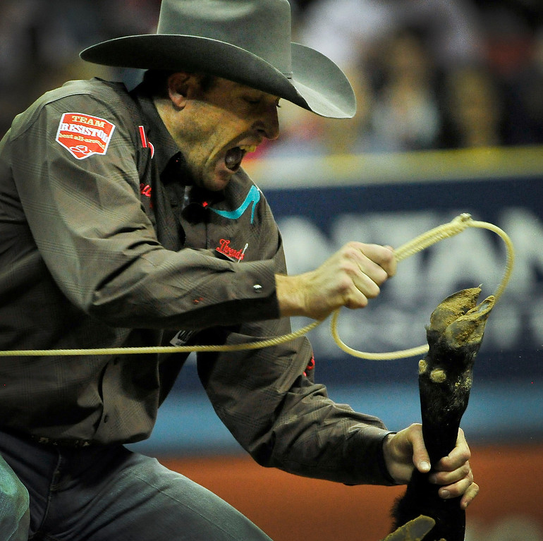 . Clint Cooper of Decatur, Texas competes in the tie-down roping during the fifth go-round of the National Finals Rodeo at the Thomas & Mack Center on Monday, Dec. 8, 2014, in Las Vegas. (AP Photo/Las Vegas Review Journal, David Becker)